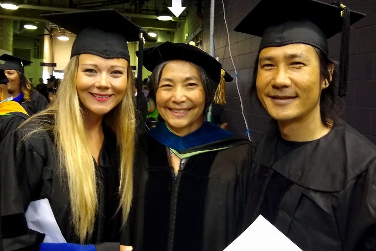 Faculty and two students at graduation
