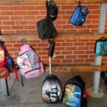 backpacks hanging on a brick wall