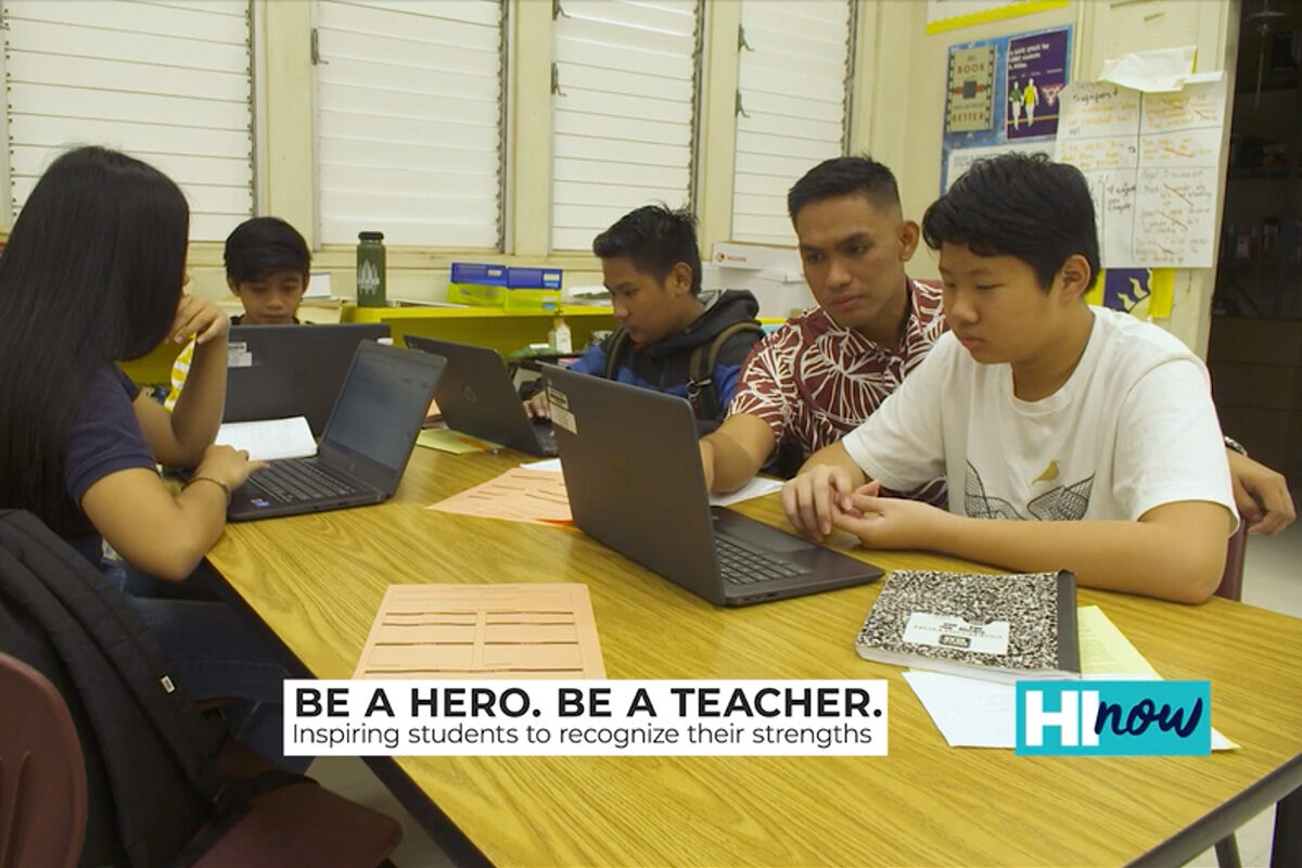 teacher assisting high school students at their desk