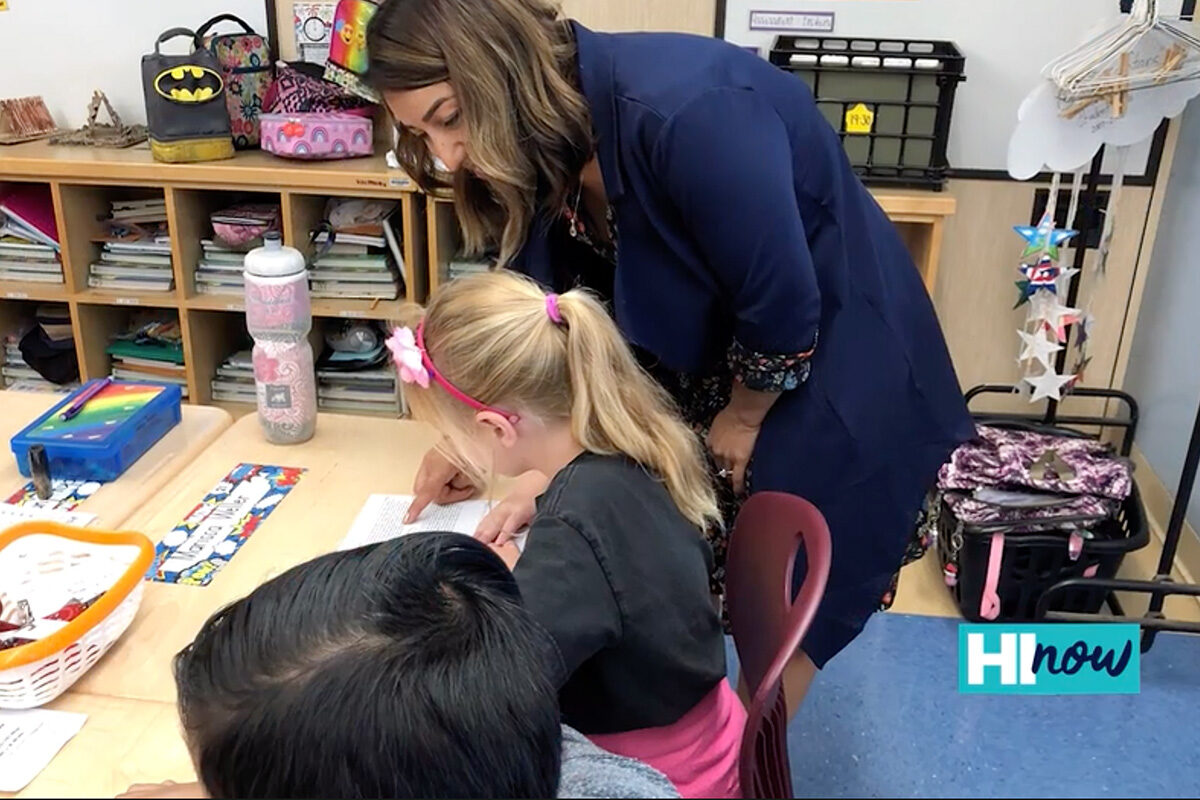 teacher leaning over elementary school student